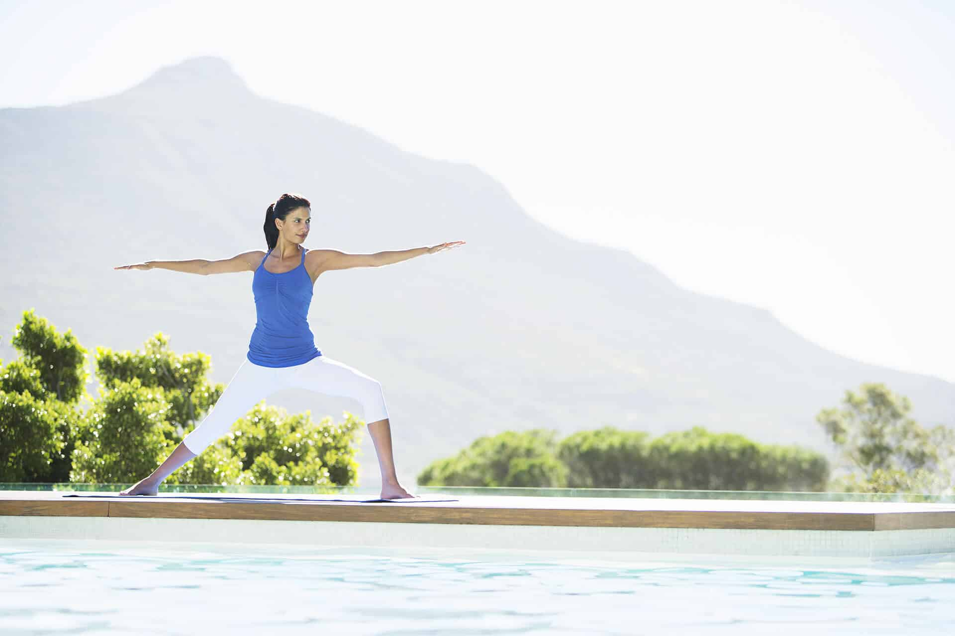 Woman practicing yoga at poolside